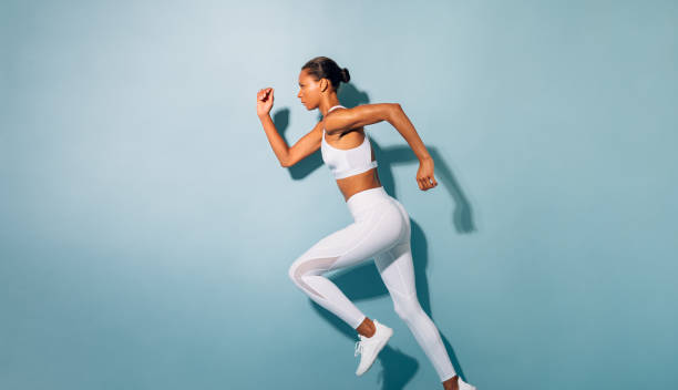 Side view of young woman running. Fitness model exercising against blue background. stock photo