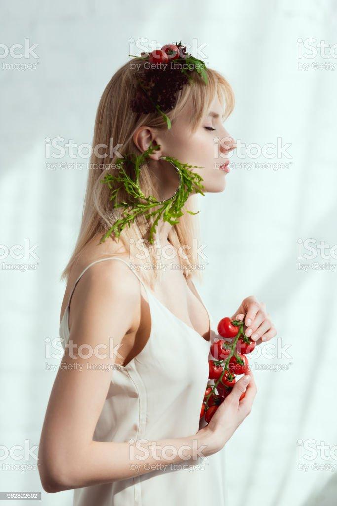 Vista lateral da jovem mulher com tomates cereja nas mãos, coroa de flores feita de legumes frescos e brinco feito de rúcula fresca, conceito de estilo de vida vegan - Foto de stock de Adulto royalty-free
