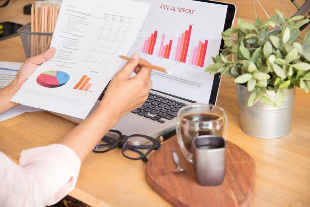 seitenansicht der junge berufstätige frau mit laptop und lesung jährlichen bericht-dokument bei der arbeit. verkauf-bericht auf notebook anzeigen. - lesen arbeitsblätter stock-fotos und bilder
