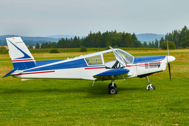 Side view of  Zlin Z-43 four-seat light airplane standing on a grass runway.  Low-wing monoplane. stock photo
