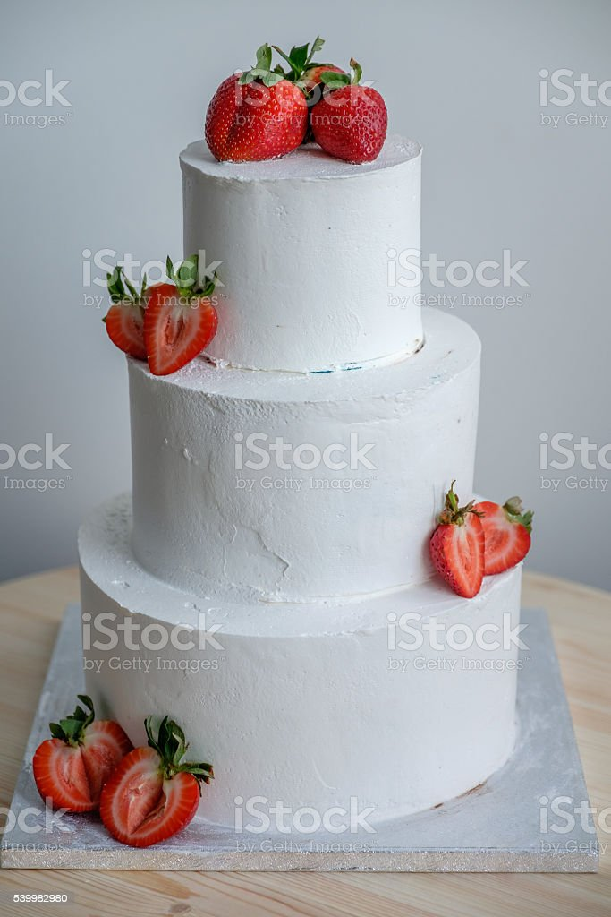 side view on big white cake decorated with red strawberry stock photo