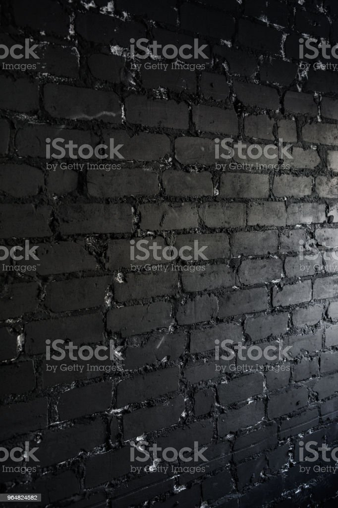 Side view on black brick wall lit by light from the window royalty-free stock photo