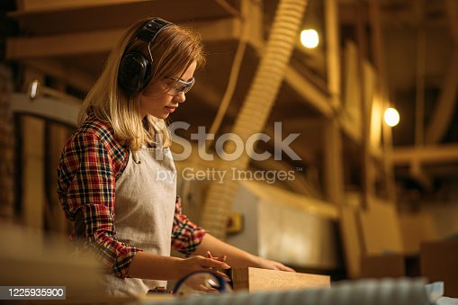 istock side view on female carpenter working 1225935900