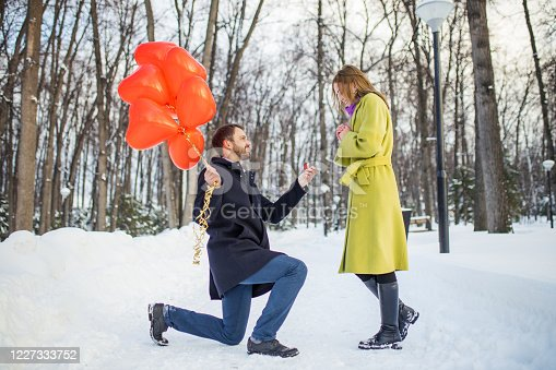 side view on beautiful lovely couple at winter street, marriage proposal by young bearded man in coat. surprised happy woman in coat look at man sitting on knees waiting for her answer, with red air balloons in hands. winter park, trees in the background, outdoors