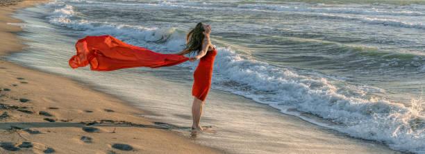 Seitenansicht auf rot gekleidete Erwachsene Frau stehen am Rand des Wassers am Strand in der Sonne mit rotem Schal im wind – Foto