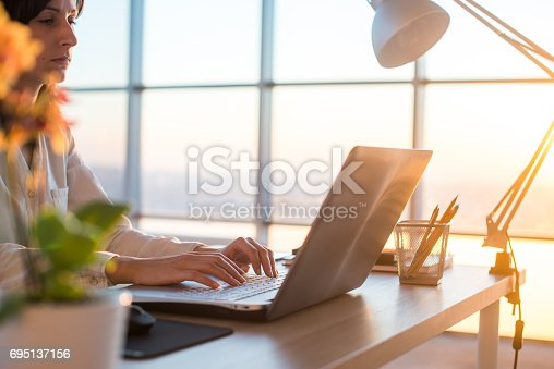 istock Side view photo of a female programmer using laptop, working, typing, surfing the internet at workplace. 695137156