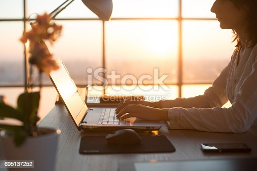 istock Side view photo of a female programmer using laptop, working, typing, surfing the internet at workplace. 695137252
