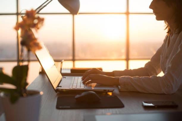 Foto da vista lateral de um programador feminino usando laptop, trabalhar, escrever, navegar na internet no local de trabalho. - foto de acervo