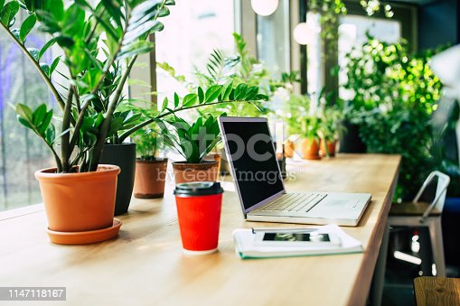 Side view photo of Digital laptop, smartphone and cup of coffee on wooden table in cafe or office