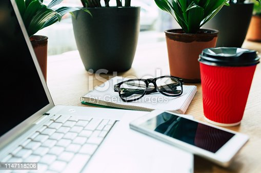 istock Side view photo of Digital laptop, smartphone and cup of coffee on wooden table in cafe or office 1147118206