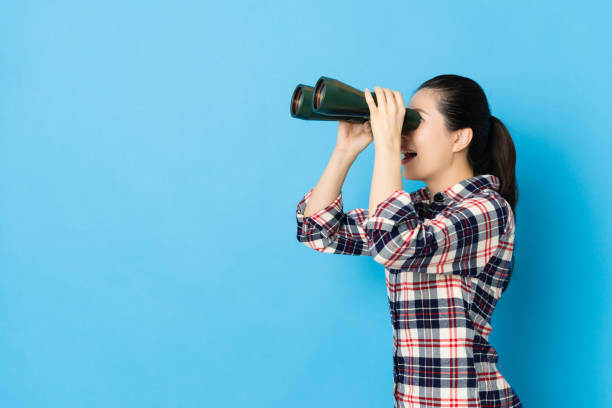 side view photo of happy girl playing telescope stock photo