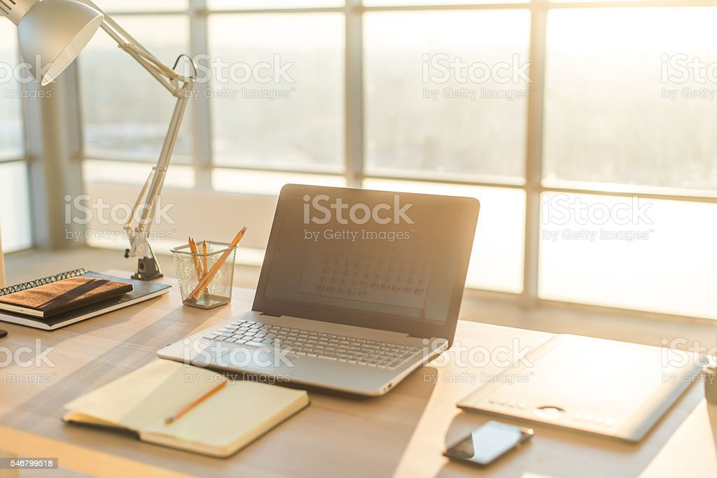 Side view picture of studio workplace with blank notebook, laptop stock photo