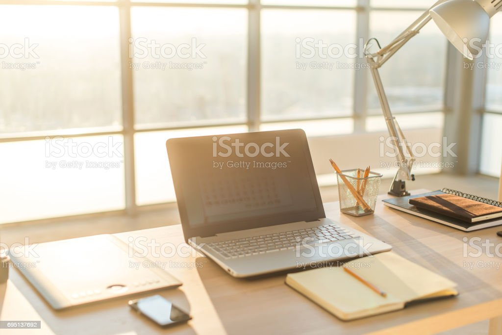 Side view picture of studio workplace with blank notebook, laptop. Comfortable work table, home office. stock photo