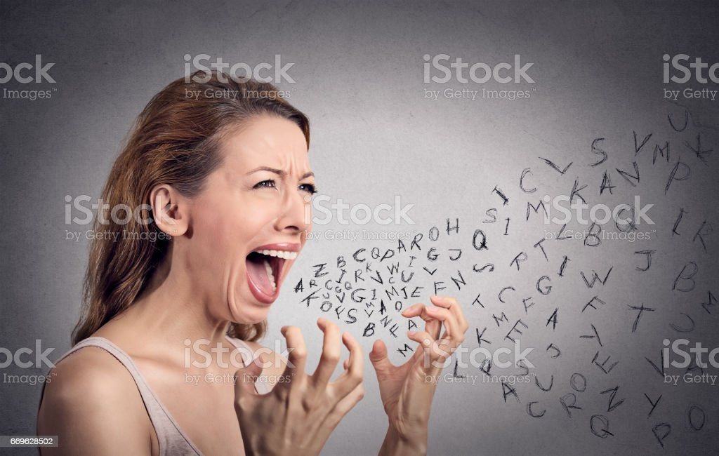Side view portrait angry woman screaming, alphabet letters coming out of open mouth stock photo