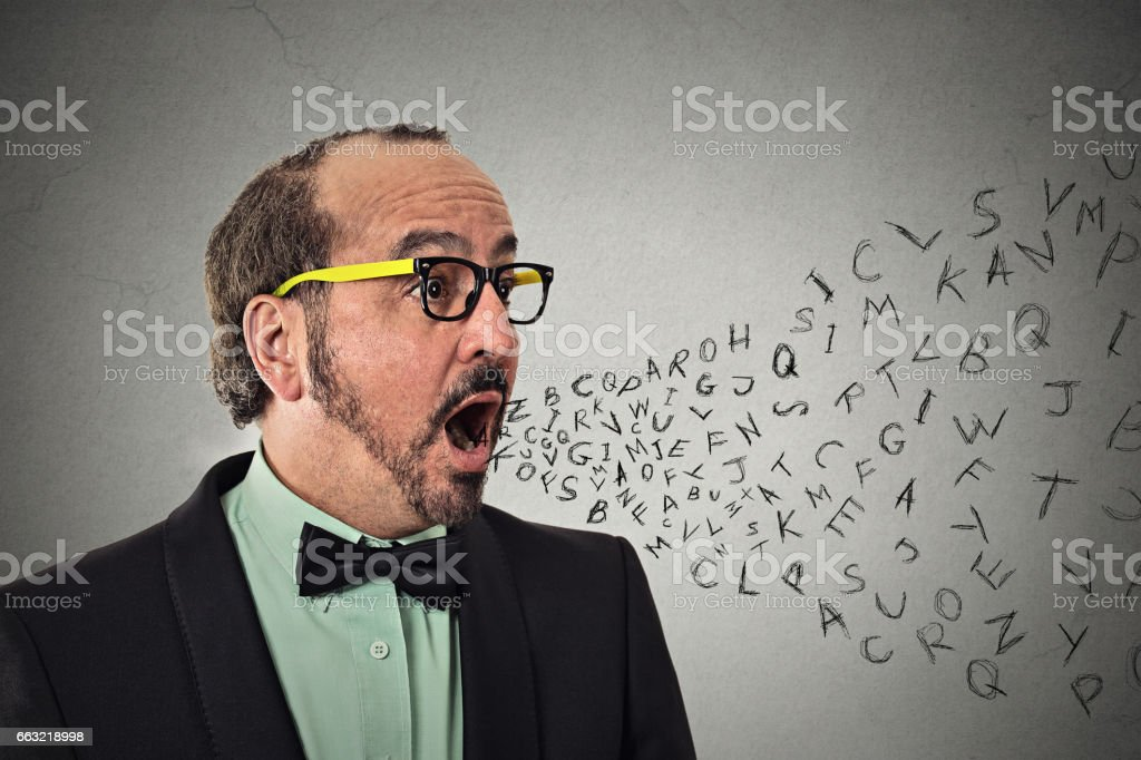 Side view portrait middle aged business man talking with alphabet letters coming out of open mouth stock photo