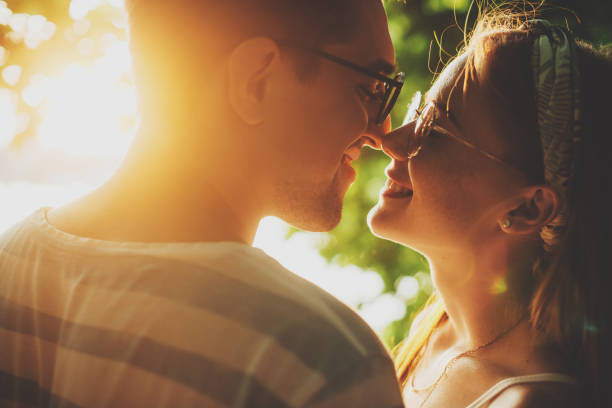 Side view portrait of a charming young couple kissing against sunset while dating in their vacation time. stock photo