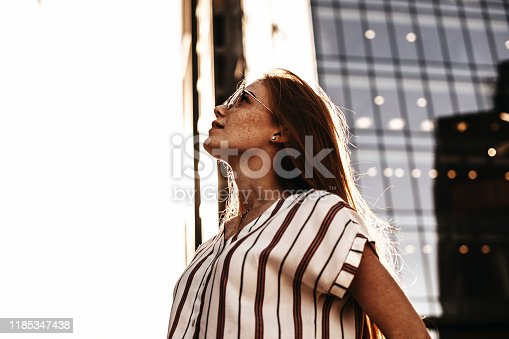 istock Side view portrait of a lovely red haired woman with freckles looking up seriously against modern business. 1185347438