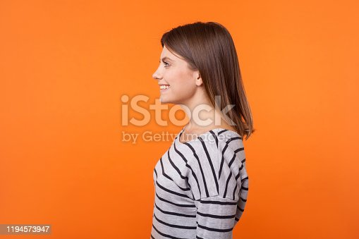 Side view portrait of adorable happy young woman with brown hair in long sleeve striped shirt standing with toothy smile and looking to the left. indoor studio shot isolated on orange background
