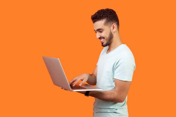 Side view portrait of cheerful brunette man working on laptop typing picture id1194574051?b=1&k=6&m=1194574051&s=612x612&w=0&h=vqnjashqdffrfdlpasprbsrruxavgv2gfwf 29ndbjg=