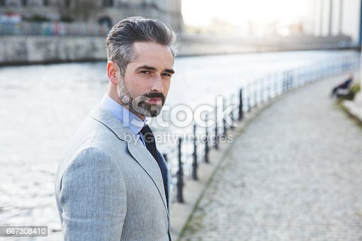 istock Side view portrait of confident businessman standing on promenade by river 667308410