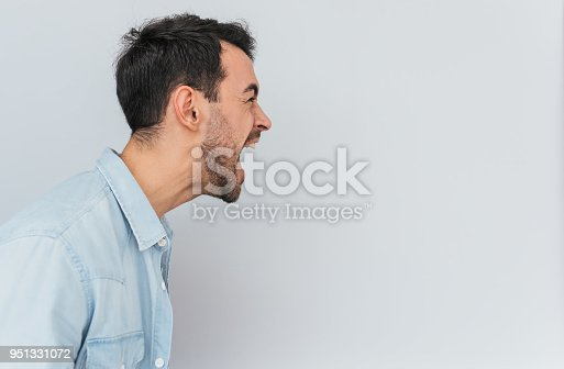 istock Side view portrait of emotional mad stylish young male screams loudly and with anger, being stressed, expresses negative emotions, isolated over white background. Emotions, feelings and people concept 951331072