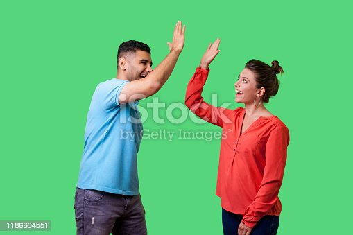 Side view portrait of excited amazed young couple in casual wear standing saying hello and giving high five, friends greeting each other, glad to meet. isolated on green background, indoor studio shot