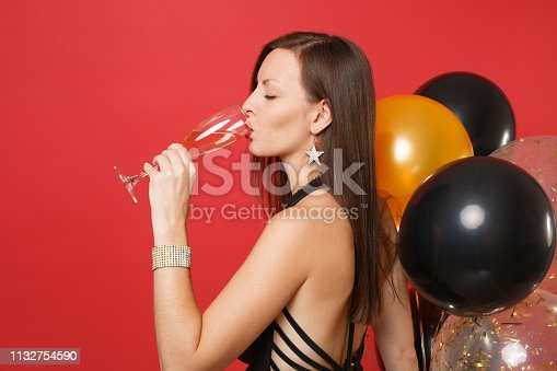 istock Side view portrait of girl in black clothes celebrating drinking champagne hold air balloons isolated on red background. International Women's Day Happy New Year birthday mockup holiday party concept. 1132754590