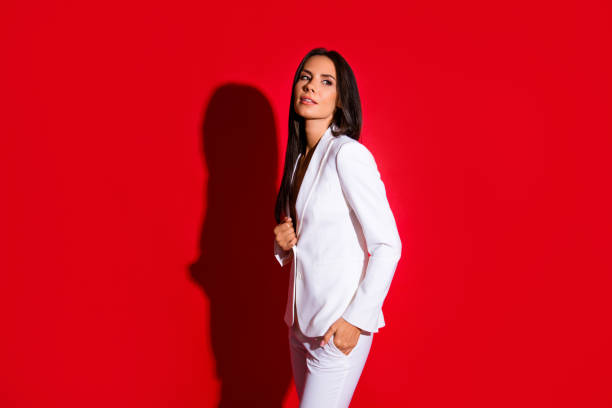 kant weergave portret van prachtige charmante vrouw in wit pak met hand in de zak op zoek weg geïsoleerd op heldere rode achtergrond - men blazer stockfoto's en -beelden