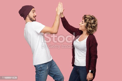 Side view portrait of happy couple of friends in casual style standing and giving five to each other with toothy smile, celebrating victory. Isolated, indoor, studio shot, pink background
