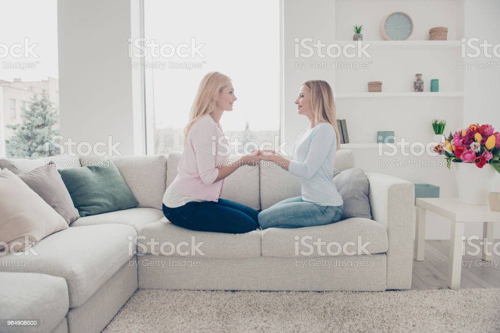 Side view portrait of lovely cute charming trendy stylish family with one parent, grandma sharing experience, sitting in modern white living room, celebrating mother's day royalty-free stock photo