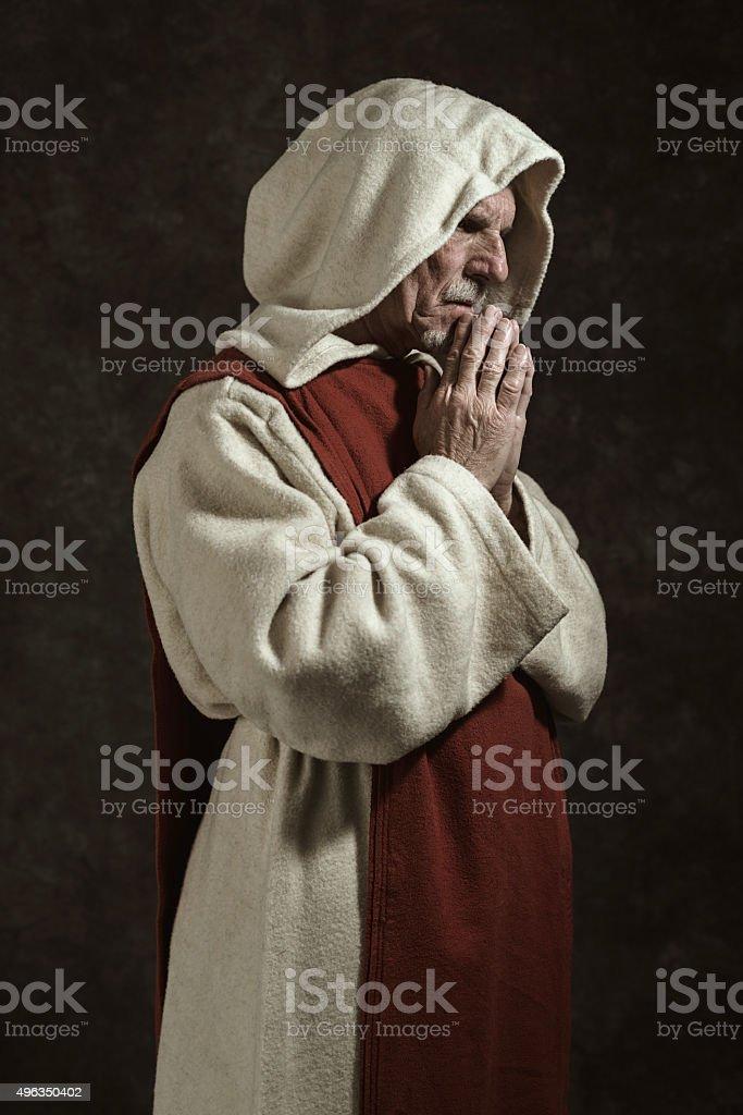 Side view portrait of praying monastic. Against dark wall. stock photo