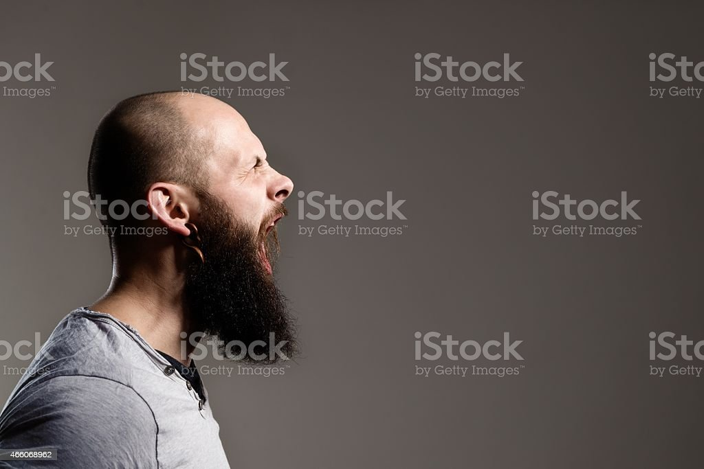 Side view portrait of screaming bearded man stock photo