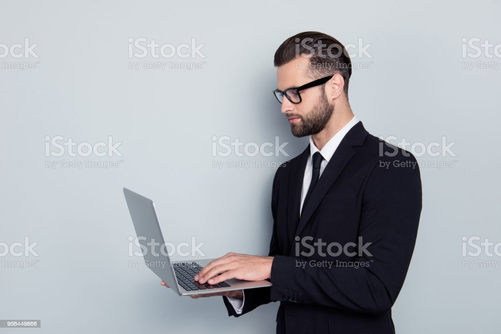 Side view portrait of smart expert clever qualified handsome stylish trendy focused concentrated confident professional successful freelancer reading using news isolated on gray background copy-space stock photo