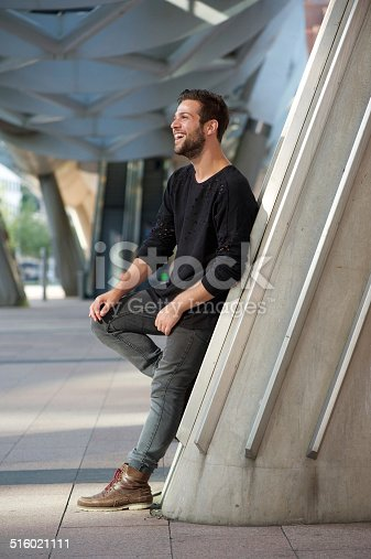 Full length side view portrait of smiling man standing outdoors