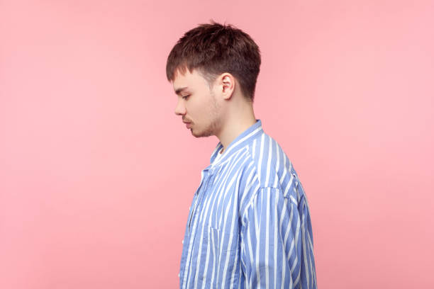 side view portrait of upset brown-haired man looking down with bowed head, depression. indoor studio shot isolated on pink background - man face down stock pictures, royalty-free photos & images