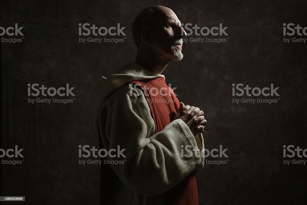 Side view portrait of wishing monastic. Against dark wall. stock photo