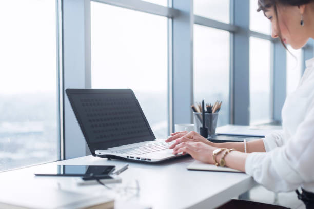 Side view portrait of woman working in home-office as teleworker, typing and surfing internet, having work day. stock photo