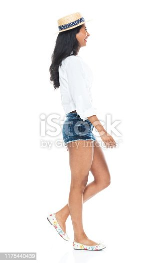 Side view / profile view / one person / full length of 20-29 years old adult beautiful / long hair latin american and hispanic ethnicity female / young women walking in front of white background wearing button down shirt / shirt / shorts who is smiling / happy / cheerful with hand by side