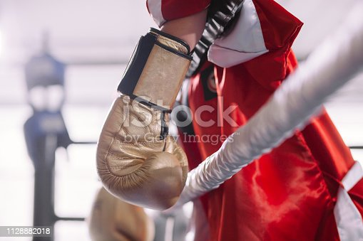 521301688 istock photo side view shot of sportswoman in red sportswear hanging her yellow boxing gloves 1128882018