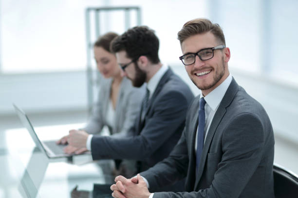 side view. smiling businessman on the background of the workplace stock photo