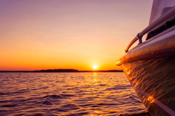 Seitenansicht Speeding Angelmotorboot mit Wassertropfen. Blaue Ozean Meer Wasser Wellen Reflexionen bei Sonnenuntergang. Motorboot im blauen Ozean. Ozean-Yacht. Sonnenuntergang auf dem Segelbootdeck – Foto