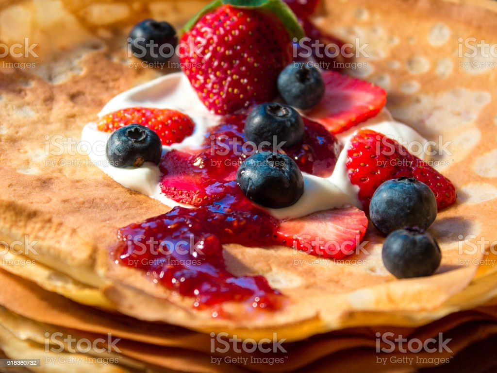 Side view stack of thin pancakes poured with sour cream and decorated with fresh strawberries and blueberries. The concept of Russian holiday Maslenitsa, Shrovetide stock photo