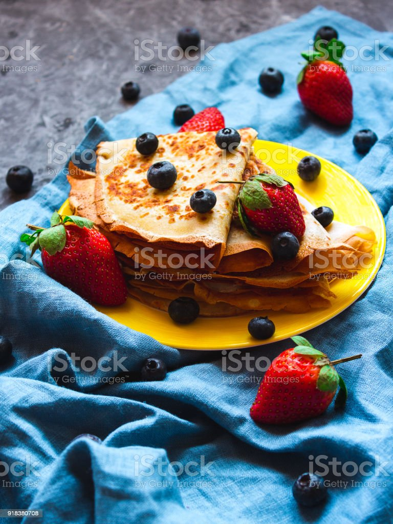 Side view stack of thin pancakesfolded in triangles and decorated with fresh strawberries and blueberries. The concept of Russian holiday Maslenitsa, Shrovetide stock photo