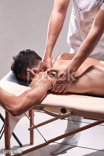 1071579572istockphoto side view, two young man, 20-29 years old, sports physiotherapy indoors in studio, photo shoot. Physiotherapist massaging patient shoulder with his hands. 1071578238