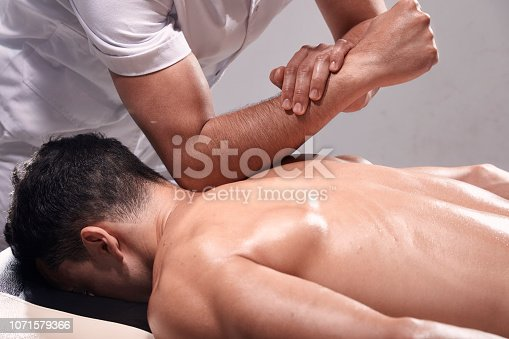 1071579572istockphoto side view, two young man, 20-29 years old, sports physiotherapy indoors in studio, photo shoot. Strong Physiotherapist hard massaging relaxed patient neck back side, with his elbow. 1071579366