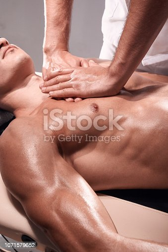 1071579572 istock photo side view, two young man, 20-29 years old, sports physiotherapy indoors in studio, photo shoot. Masseur massaging athlete mans chest, muscular body, hands close-up. 1071579652