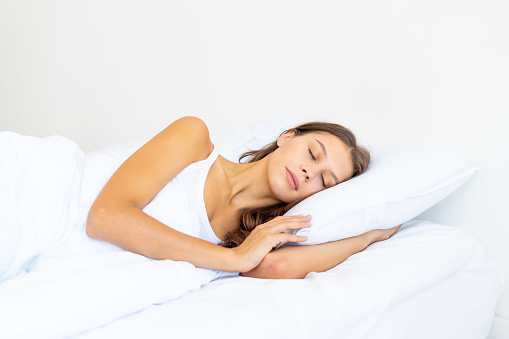 Side view waist portrait of beautiful sleeping woman in bed. Female with long hair resting, good night sleep concept, enjoying fresh soft bedding linen and mattress in bedroom