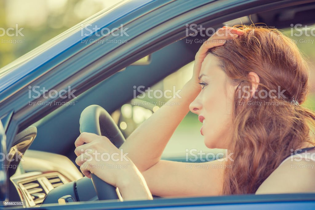 Side view window portrait displeased young stressed angry pissed off woman driving car stock photo