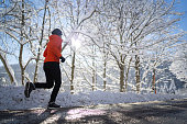 fit sporty female athlete 45 years old woman running jogging on road with slush on cold sunny sunshine winter day snow snow covered trees endurance training side view