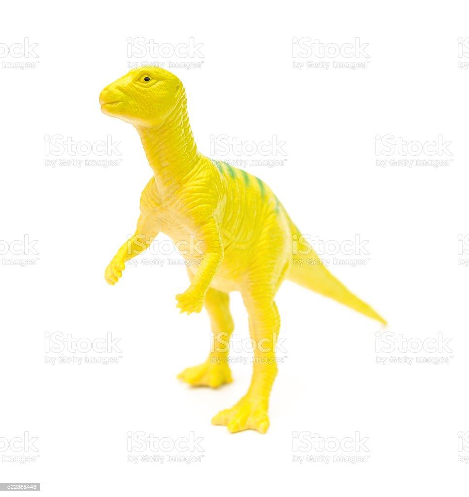 Vista lateral de plástico de brinquedos de dinossauro na amarela sobre um fundo branco - foto de acervo